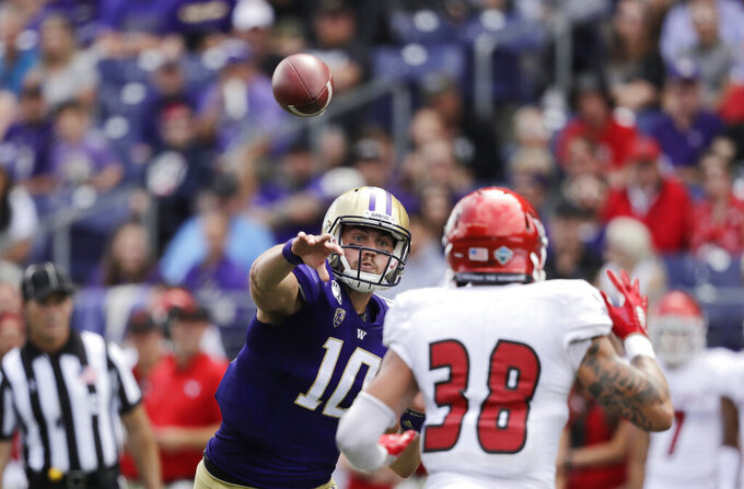 Washington quarterback Jacob Eason (10) throws a touchdown pass as Eastern Washington's Joe Lang defends in the first half of an NCAA college football game Saturday, Aug. 31, 2019, in Seattle. (AP Photo/Elaine Thompson)