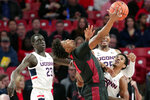 Houston guard Nate Hinton, front, reaches for a rebound in front of center Josh Carlton (25) and Connecticut guard Christian Vital, right, during the first half of an NCAA college basketball game Thursday, Jan. 23, 2020, in Houston. (AP Photo/Michael Wyke)