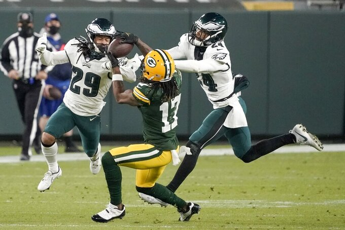 Green Bay Packers' Davante Adams catches a pass with Philadelphia Eagles' Avonte Maddox (29) and Darius Slay (24) defending during the second half of an NFL football game Sunday, Dec. 6, 2020, in Green Bay, Wis. (AP Photo/Morry Gash)