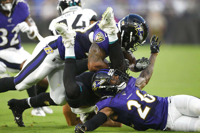 The legs of Jacksonville Jaguars tight end Geoff Swaim go up as he is tackled by Baltimore Ravens cornerback Maurice Canady (26) and linebacker Chris Board during the first half of an NFL football preseason game, Thursday, Aug. 8, 2019, in Baltimore. (AP Photo/Nick Wass)