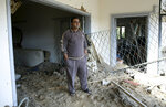 Read Tahtawi inspects the damage of his building which was destroyed during an Israeli airstrike on the offices of Hamas leader Ismail Haniyeh, in Gaza City, Tuesday, March 26, 2019. A tense quiet took hold Tuesday morning after a night of heavy fire as Israeli aircraft bombed targets across the Gaza Strip and Gaza militants fired rockets into Israel in what threatened to devolve into a major conflict two weeks before the Israeli election. (AP Photo/Adel Hana)