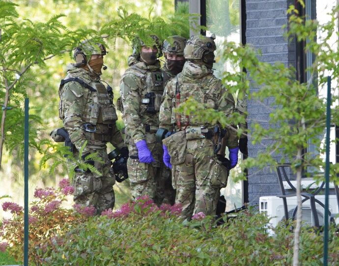 RCMP officers prepare to enter an apartment complex in connection with the mailing of ricin to President Trump Monday, Sept. 21, 2020 in St. Hubert, Canada. (Ryan Remiorz/The Canadian Press via AP)