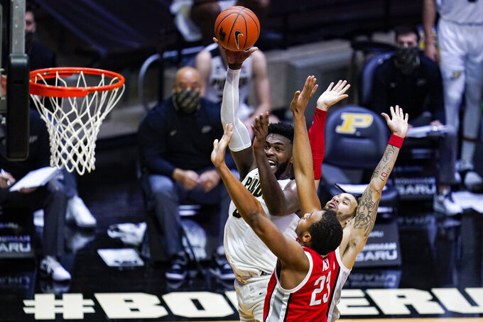 Purdue forward Trevion Williams (50) shoots over Ohio State center Zed Key (23) and guard Duane Washington Jr. (4) during the second half of an NCAA college basketball game in West Lafayette, Ind., Wednesday, Dec. 16, 2020. (AP Photo/Michael Conroy)