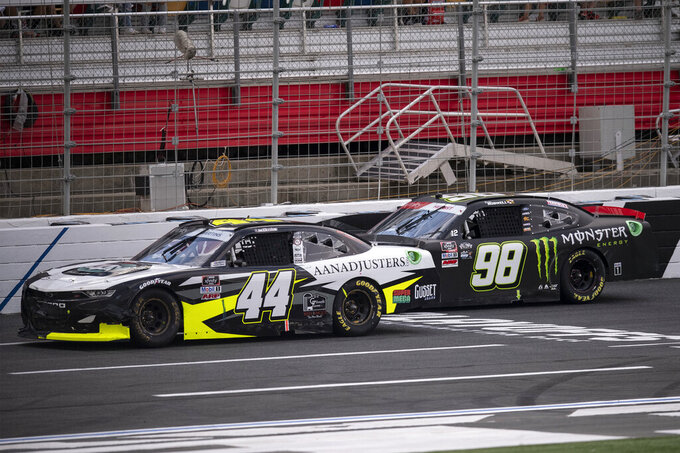 NASCAR Xfinity Series driver Tommy Joe Martins (44) passes Riley Herbst (98) during the NASCAR Xfinity auto racing race at the Charlotte Motor Speedway Saturday, Oct. 9, 2021, in Concord, N.C. (AP Photo/Matt Kelley)