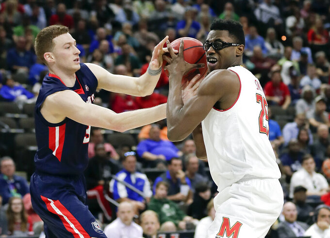 Belmont 's Dylan Windler, left, tries to steal the ball from Maryland 's Jalen Smith during the second half of a first round men's college basketball game in the NCAA Tournament in Jacksonville, Fla., Thursday, March 21, 2019. (AP Photo/John Raoux)