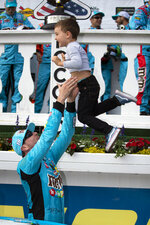 Kyle Busch, left, tosses his son, Brexton Busch, 4, into the air in victory lane after winning a NASCAR Cup Series auto race at Pocono Raceway, Sunday, June 2, 2019, in Long Pond, Pa. (AP Photo/Matt Slocum)