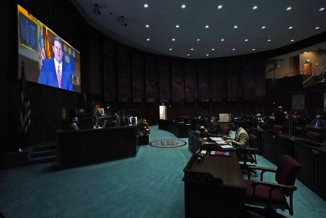 In a darkened and nearly empty Arizona House of Representatives, Republican Gov. Doug Ducey delivers a remote state of the state address during the opening of the Arizona Legislature at the state Capitol Monday, Jan. 11, 2021, in Phoenix. (AP Photo/Ross D. Franklin, Pool)
