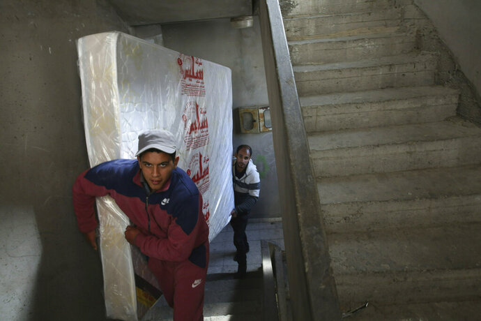 In this April 21, 2019 photo, Palestinian groom Yehiya Taleb, center, move a mattress, part of his wedding furniture, to his apartment in Shati refugee camp, Gaza City. Hundreds of young men in the Gaza Strip have turned to a small industry of lenders to help them pay for their weddings. Taleb got a job working as a waiter at a cafe earning about $180 a month, but that amount was not enough to cover wedding expenses so he took out a $2,000 package through the Farha Project, one of the wedding financing companies. (AP Photo/Adel Hana)