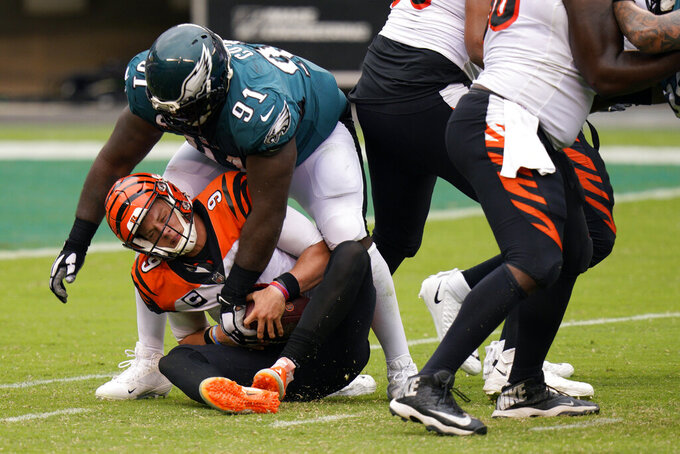 Cincinnati Bengals' Joe Burrow (9) is tackled by Philadelphia Eagles' Fletcher Cox (91) during overtime of an NFL football game, Sunday, Sept. 27, 2020, in Philadelphia. (AP Photo/Chris Szagola)