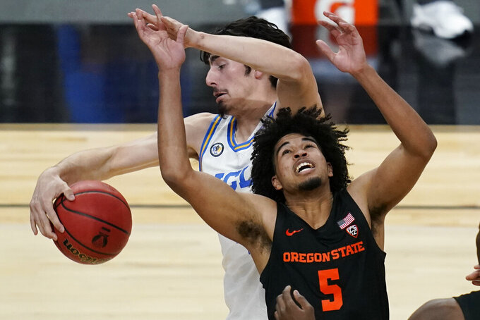 UCLA's Jaime Jaquez Jr., left, fouls Oregon State's Ethan Thompson (5) during the second half of an NCAA college basketball game in the quarterfinal round of the Pac-12 men's tournament Thursday, March 11, 2021, in Las Vegas. (AP Photo/John Locher)