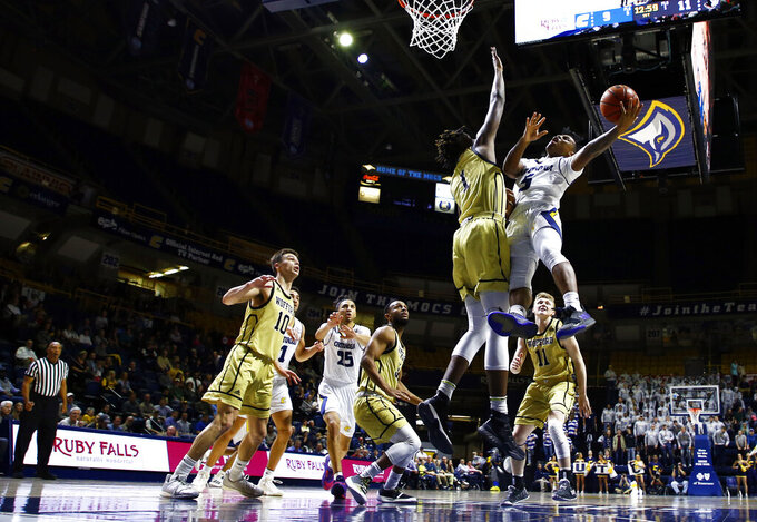 Chattanooga guard Donovann Toatley (5) shoot past Wofford forward Chevez Goodwin (1) during the first half of an NCAA college basketball game Thursday, Feb. 28, 2019, in Chattanooga, Tenn. (AP photo/Wade Payne)