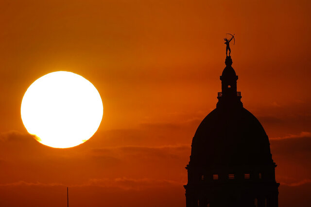 The Kansas Statehouse stands against the sky as the sun sets in the distance Monday, April 27, 2020, in Topeka, Kan. Kansas remains under stay-at-home orders until May 3 in an effort to stem the spread of the coronavirus. (AP Photo/Charlie Riedel)