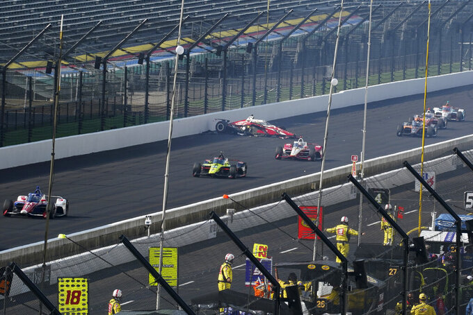 Spencer Pigot car sits on the track after crashing during the Indianapolis 500 auto race at Indianapolis Motor Speedway, Sunday, Aug. 23, 2020, in Indianapolis. (AP Photo/Darron Cummings)