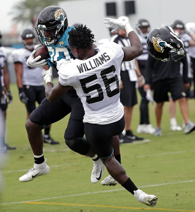 Jacksonville Jaguars linebacker Quincy Williams (56) loses his helmet as he tackles running back Ryquell Armstead, left, during an NFL football practice at the teams training facility, Thursday, Aug. 1, 2019, in Jacksonville, Fla. (AP Photo/John Raoux)