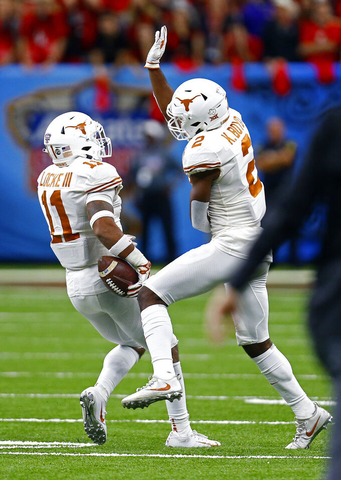 Texas defensive back P.J. Locke III (11) celebrates his interception with defensive back Kris Boyd (2) during the second half of the Sugar Bowl NCAA college football game against Georgia in New Orleans, Tuesday, Jan. 1, 2019. (AP Photo/Butch Dill)