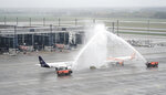 Planes of the airlines Lufthansa and Easyjet stand under a fountain from the airport's fire brigade in front of Terminal 1, to celebrate the opening of the new airport Berlin Brandenburg 'Willy Brandt', BER, in Schoenefeld near Berlin, Germany, Saturday, Oct. 31. The airport will open on 31.10.2020 after a long delay. (Kay Nietfeld/POOL via AP)