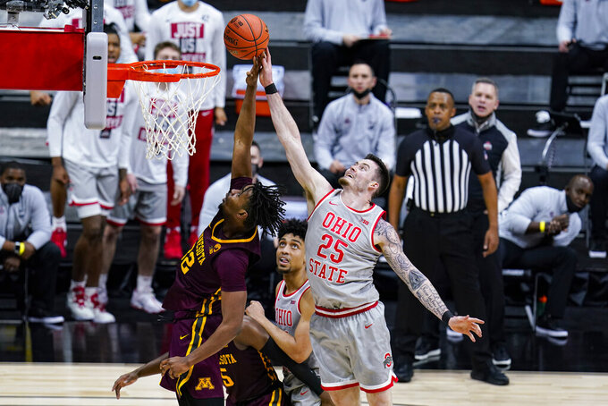 Minnesota center Sam Freeman (32) and Ohio State forward Kyle Young (25) go up for a rebound in the second half of an NCAA college basketball game at the Big Ten Conference tournament in Indianapolis, Thursday, March 11, 2021. (AP Photo/Michael Conroy)
