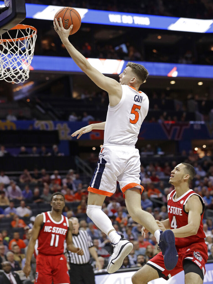 Virginia's Kyle Guy (5) drives past North Carolina State's Jericole Hellems (4) during the first half of an NCAA college basketball game in the Atlantic Coast Conference tournament in Charlotte, N.C., Thursday, March 14, 2019. (AP Photo/Chuck Burton)