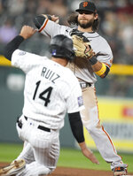 San Francisco Giants shortstop Brandon Crawford, back, throws to first base after putting out Colorado Rockies' Rio Ruiz at second base on the front end of a double play hit into by Raimel Tapia to end the fifth inning of a baseball game Tuesday, Sept. 7, 2021, in Denver. (AP Photo/David Zalubowski)