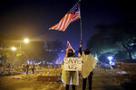 FILE - In this Nov. 18, 2019, file photo, protesters hold British and American flags and a sign reading