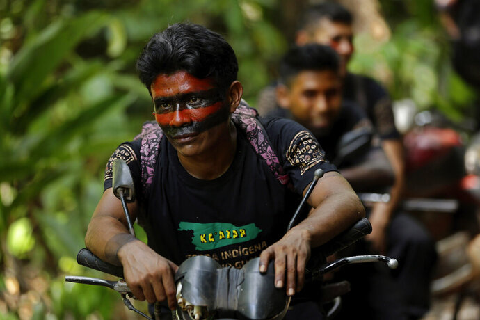 Tenetehara Indigenous man Gilberto Tembe waits on his motorcycle as fellow members of the Ka'Azar, or Forest Owners, clear away a tree felled by illegal loggers, as they patrol their lands on the Alto Rio Guama reserve in Para state, near the city of Paragominas, Brazil, Tuesday, Sept. 8, 2020. Three Tenetehara Indigenous villages are patrolling to guard against illegal logging, gold mining, ranching, and farming as increasing encroachment and lax government enforcement during COVID-19 have forced the tribe to take matters into their own hands. (AP Photo/Eraldo Peres)