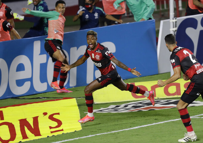 Flamengo's Bruno Henrique, center, scores his side's opening goal against Sao Paulo during the Brazilian championship final soccer match at the Morumbi stadium, Sao Paulo, Brazil, Thursday, Feb. 25, 2021. (AP Photo/Andre Penner)