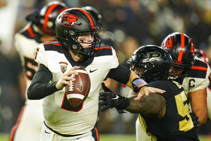 Oregon State quarterback Sam Noyer (6) escapes from Purdue defensive tackle Branson Deen (58) during the first half of an NCAA college football game in West Lafayette, Ind., Saturday, Sept. 4, 2021. (AP Photo/Michael Conroy)