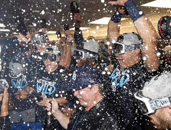 Tampa Bay Rays players celebrate in the clubhouse after they defeated the Toronto Blue Jays and clinched an MLB American League wild-card berth in Toronto, Friday, Sept. 27, 2019. (Fred Thornhill/The Canadian Press via AP)