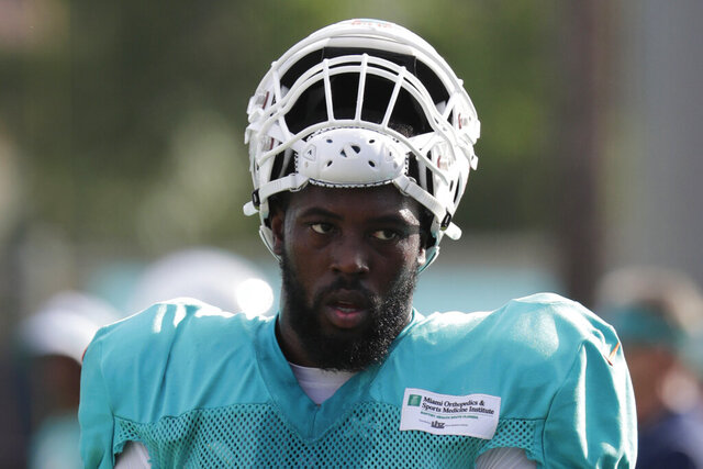 FILE - In this July 30, 2018, file photo, Miami Dolphins defensive end Charles Harris (90) walks on the field at the NFL football team's training camp in Davie, Fla. Former first-round draft pick Charles Harris was traded Friday, May 1, 2020, after three unproductive seasons by the Miami Dolphins to the Atlanta Falcons for a seventh-round choice in 2021. (AP Photo/Lynne Sladky, File)