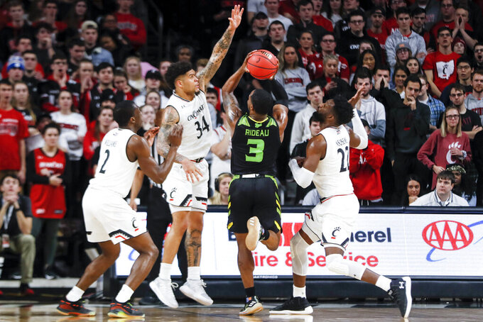 South Florida's LaQuincy Rideau (3) shoots against Cincinnati's Keith Williams (2), Jarron Cumberland (34) and Eliel Nsoseme (22) in the first half of an NCAA college basketball game, Tuesday, Jan. 15, 2019, in Cincinnati. (AP Photo/John Minchillo)