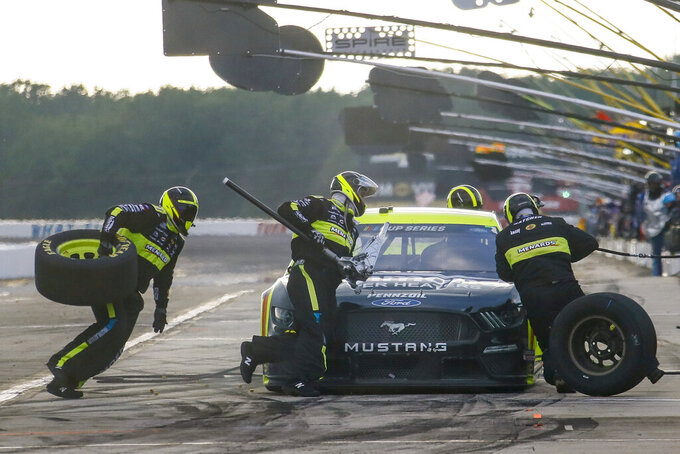 Crew members for Ryan Blaney scramble around the car in a pit stop during a NASCAR Cup Series auto race at Pocono Raceway, Sunday, June 28, 2020, in Long Pond, Pa. (AP Photo/Matt Slocum)