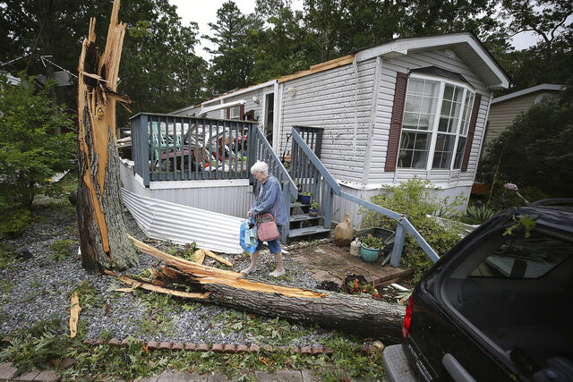 Ellen Mallen, who lives in a mobile home court, carefully leaves her home after a suspected tornado spawned by Isaias struck Marmora, N.J., Tuesday, Aug 4, 2020. (David Maialetti/The Philadelphia Inquirer via AP)