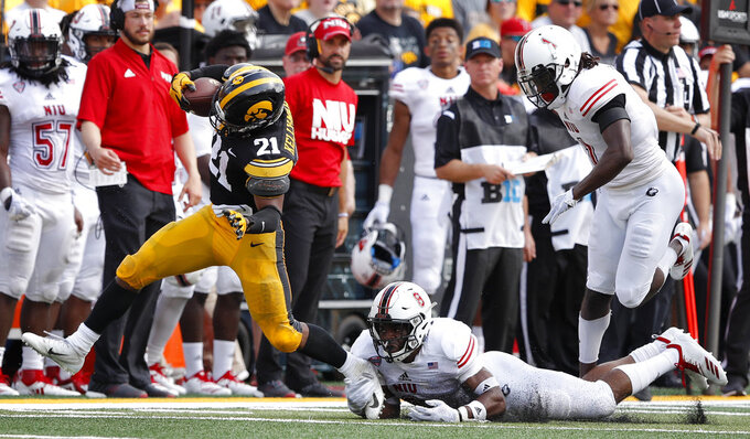 Iowa running back Ivory Kelly-Martin,left, runs from Northern Illinois safety Mykelti Williams, center, and cornerback Albert Smalls, right, during the first half of an NCAA college football game, Saturday, Sept. 1, 2018, in Iowa City, Iowa. (AP Photo/Charlie Neibergall)