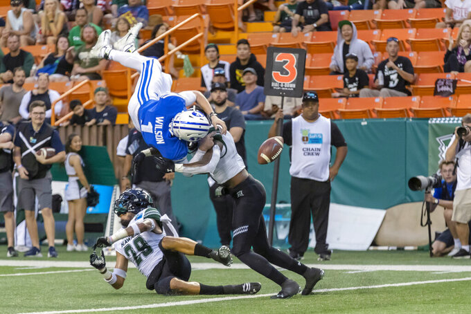BYU quarterback Zach Wilson (1) loses the football on a hit by Hawaii defensive back Eugene Ford, right, as Wilson tried to leap into the end zone during the second half of the Hawaii Bowl NCAA college football game Tuesday, Dec. 24, 2019, in Honolulu. Hawaii recovered the football in the end zone for a touchback. (AP Photo/Eugene Tanner)