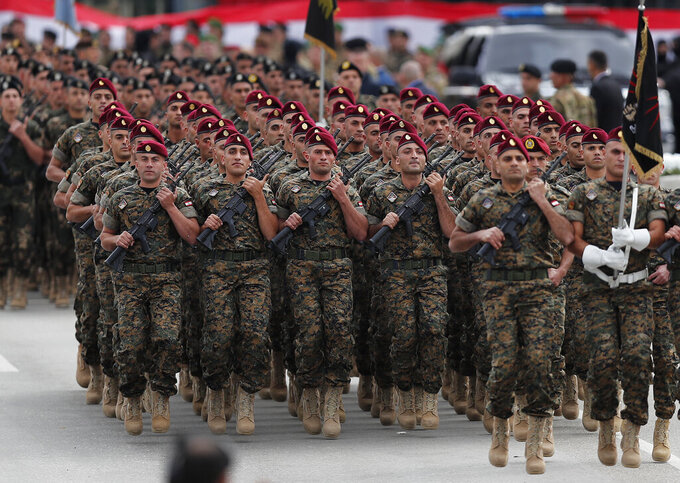 File - in this November 22, 2018 file photo, Lebanese army special forces march during a military parade to mark the 74th anniversary of Lebanon's independence from France in downtown Beirut, Lebanon. The currency collapse has wiped out the salaries of the U.S.-backed Lebanese military, placed unprecedented pressure on the army's operational capabilities with some of the highest attrition rates over the past two years, and raised concerns about its ability to continue playing a stabilizing role while sectarian tensions and crime are on the rise. (AP Photo/Hussein Malla, File)