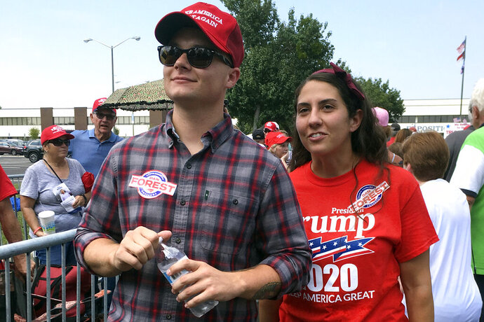 Ashley Arentz, 28, of Jacksonville, N.C., waits in line with friend Jonathan Ritter to enter a rally that President Donald Trump staged for Republican congressional candidate Dan Bishop in Fayetteville, N.C., Monday, Sept. 9, 2019. Arentz, a Marine, said she signed up to vote at the rally. Trump's campaign is on the hunt for political unicorns: Trump's team is searching for people in battleground states who support the president but didn't vote in 2016. (AP Photo/Alan Fram)