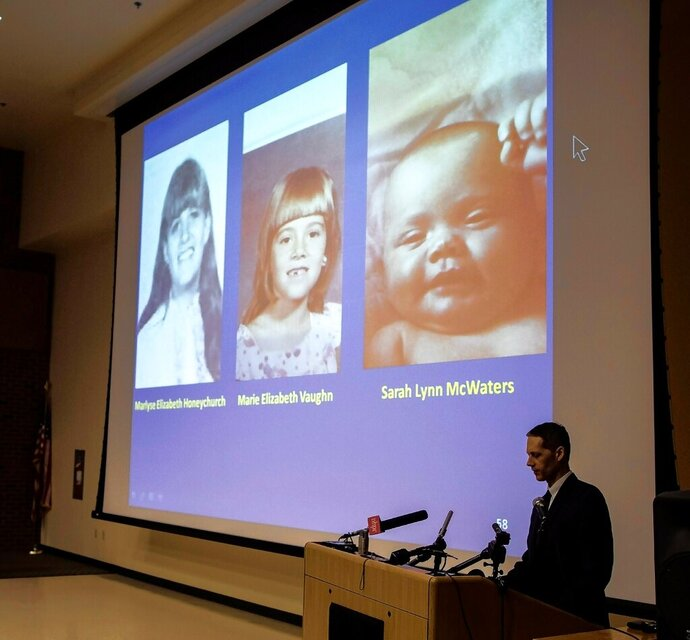 FILE -- In this Thursday, June 6, 2019 file photo New Hampshire Senior Assistant Attorney General Jeffery Strelzin, bottom right, stands in front of projected photos of three identified murder victims, Marlyse Honeychurch, left, and her daughters Marie Elizabeth Vaughn, center, and Sarah Lynn McWaters, right, during a news conference at the Department of Safety, in Concord, N.H. A graveside service is planned in New Hampshire, Saturday, Nov. 9, 2019, for Honeychurch, and Vaughn, who were identified decades after their remains were discovered in a barrel in 1985. Authorities believe convicted killer Terry Peder Rasmussen, who died in a California prison in 2010, is responsible for the deaths. (Michael Pezone/The Concord Monitor via AP, File)