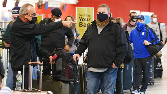 Travelers wait in line at the ticket counter before traveling from Cleveland Hopkins International Airport, Wednesday, Nov. 25, 2020, in Cleveland. (AP Photo/Tony Dejak)