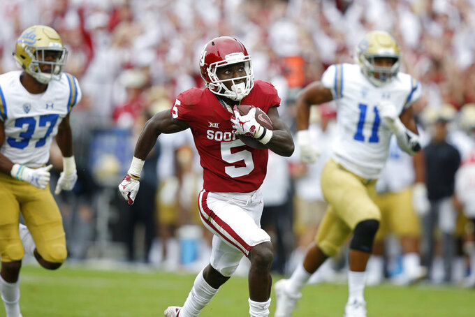 FILE - In this Sept. 8, 2018, file photo, Oklahoma wide receiver Marquise Brown (5) runs away from UCLA defensive back Quentin Lake (37) and linebacker Keisean Lucier-South (11) for a touchdown in the first quarter of an NCAA college football game in Norman, Okla. Brown already is the national leader with six catches of at least 40 yards--those account for his five touchdowns. Brown has caught 24 passes for 544 yards, a Big 12-best 22.7 yards per catch. Oklahoma plays Texas this week. (AP Photo/Sue Ogrocki, File)