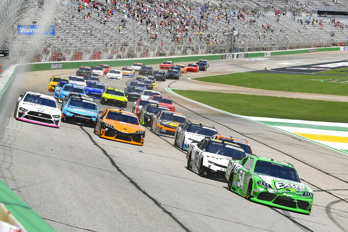 A NASCAR Xfinity Series auto race starts, led by Kyle Busch, right, who is followed by AJ Allmendinger as they go into Turn  1, Saturday, July 10, 2021, in Hampton, Ga. (AP Photo/John Amis)