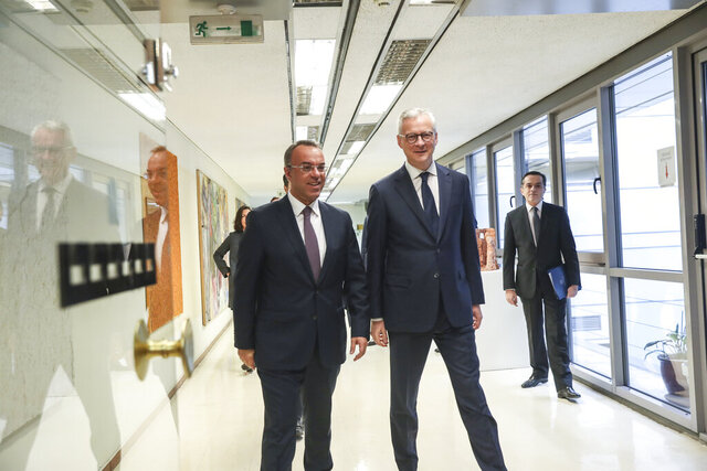 Greece's Finance Minister Christos Staikouras, left, walks with his French counterpart Bruno Le Maire before their meeting in Athens, on Tuesday, Feb. 25, 2020. (AP Photo/Petros Giannakouris)