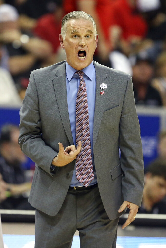 San Diego State head coach Brian Dutcher instructs his team against Utah State during the first half of an NCAA college basketball game for the Mountain West Conference men's tournament championship Saturday, March 7, 2020, in Las Vegas. (AP Photo/Isaac Brekken)