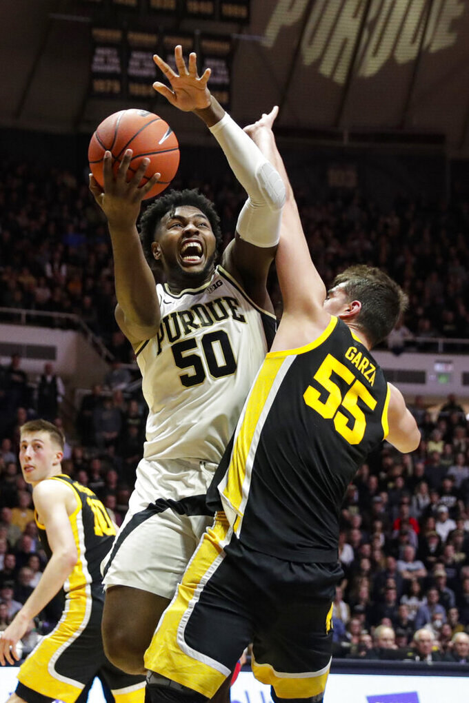 Purdue forward Trevion Williams (50) shoots over Iowa center Luka Garza (55) during the second half of an NCAA college basketball game in West Lafayette, Ind., Wednesday, Feb. 5, 2020. Purdue defeated Iowa 104-68. (AP Photo/Michael Conroy)