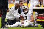 New Orleans Saints wide receiver Taysom Hill is tended to after being injured in the first half of an NFL football gameagainst the Washington Football Team, Sunday, Oct. 10, 2021, in Landover, Md. (AP Photo/Alex Brandon)