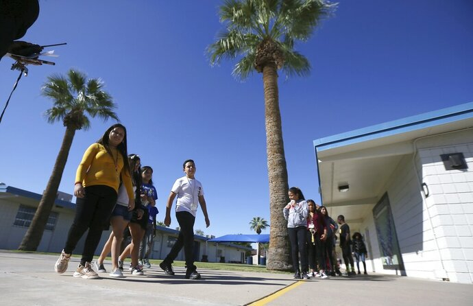 File - In this Oct. 17, 2019, file photo, Students walk to class on campus at Valencia Newcomer School in Phoenix. The school is among a handful of such public schools in the United States dedicated exclusively to helping some of the thousands of children who arrive in the country annually. Arizona Gov. Doug Ducey told President Donald Trump's administration Friday, Dec. 6, 2019, the state will continue its tradition of welcoming refugees, cheering resettlement agencies that have lobbied the state and local governments to keep opening their arms to people fleeing war and other horrific situations in their native countries. (AP Photo/Ross D. Franklin, File)