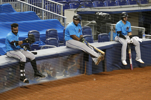 FILE - In this July 12, 2020, file photo, Miami Marlins' Jonathan Villar, left, Jesus Aguilar, center, and Jon Berti wait to bat during a baseball scrimmage at Marlins Park in Miami. Marlins CEO Derek Jeter blamed the team's coronavirus outbreak on a collective false sense of security that made players lax about social distancing and wearing masks. Infected were 21 members of the team's traveling party, including at least 18 players. None is seriously ill, Jeter said Monday, and he expects all to return this season.  (AP Photo/Lynne Sladky, File)