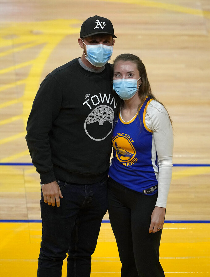 """Shelby Delaney, right, an intensive care unit nurse at Oakland's Alta Bates Summit Medical Center, and her husband, Robert Crowley, pose for a photo before the Golden State Warriors and Sacramento Kings NBA basketball game on Sunday, April 25, 2021, in San Francisco. Last spring, Stephen Curry placed a FaceTime call to Delaney and her colleagues at Oakland's Alta Bates Summit Medical Center after learning she was wearing his No. 30 jersey under her scrubs as inspiration to get through each trying day of the pandemic. Delaney wore the uniform again as she and Crowley sat on the floor for Sunday's game after a season ticket holder who couldn't attend gifted her the seats. Inside the jersey reads, """"I Can Do All Things."""" (AP Photo/Tony Avelar)"""