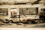 Scorched vehicles rest at an auto shop destroyed by the Almeda Fire in Talent, Ore., on Wednesday, Sept. 16, 2020. (AP Photo/Noah Berger)