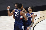 Connecticut's Josh Carlton (25) celebrates with Isaiah Whaley, rear, and James Bouknight right, during the first half of an NCAA college basketball game against Southern California, Thursday, Dec. 3, 2020, in Uncasville, Conn. (AP Photo/Jessica Hill)