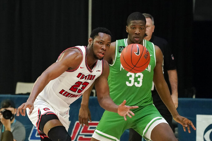 Western Kentucky center Charles Bassey (23) fights for a loose ball with North Texas forward Abou Ousmane (33) during the first half of the championship game in the NCAA Conference USA men's basketball tournament Saturday, March 13, 2021, in Frisco, Texas. (AP Photo/Tony Gutierrez)